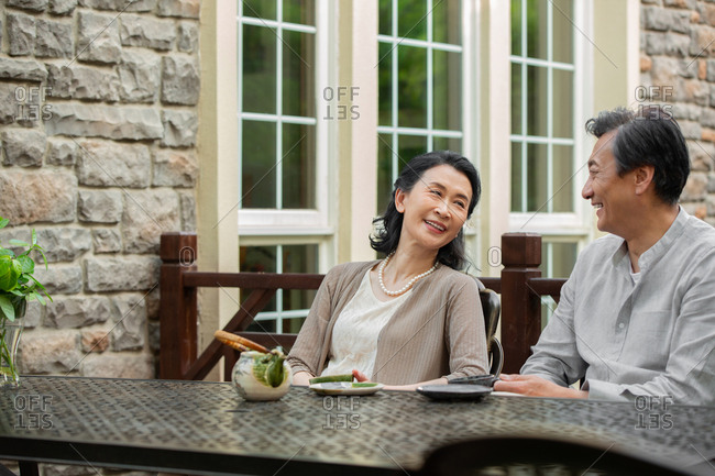 The elderly couple sitting in the yard for tea