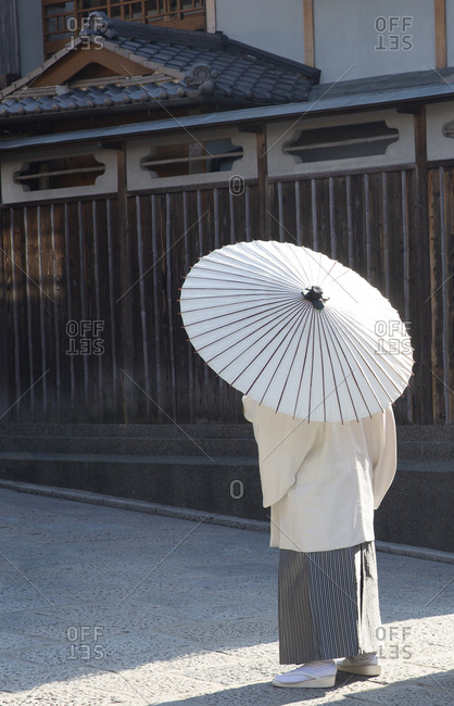 Man dressed in traditional clothing and walking with parasol in Old Town, Kyoto, Japan