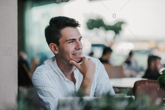 Handsome twenty-five year old man sitting in a bar and smiling