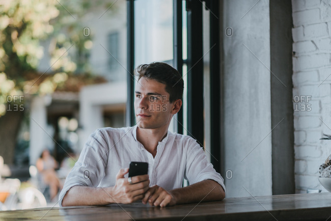 Handsome man sitting in a bar alone while holding cellphone