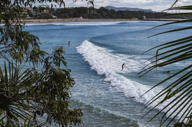 Noosa, Queensland, Australia - July 8, 2019: Stand-up paddleboarders in the ocean