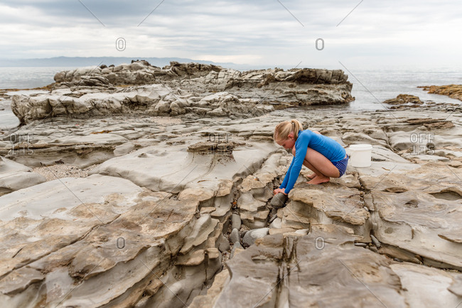 Girl exploring rock pools on the coast in the summer