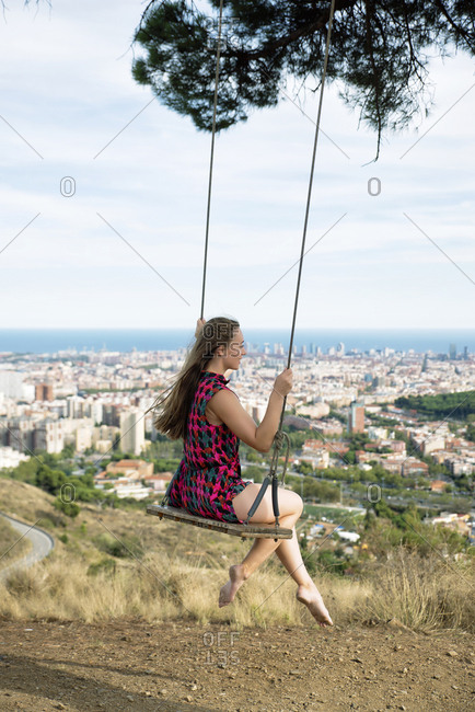 Side view of carefree woman sitting on rope swing against cityscape