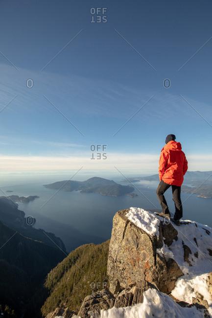 Male hiker standing on mountain peak overlooking ocean and islands