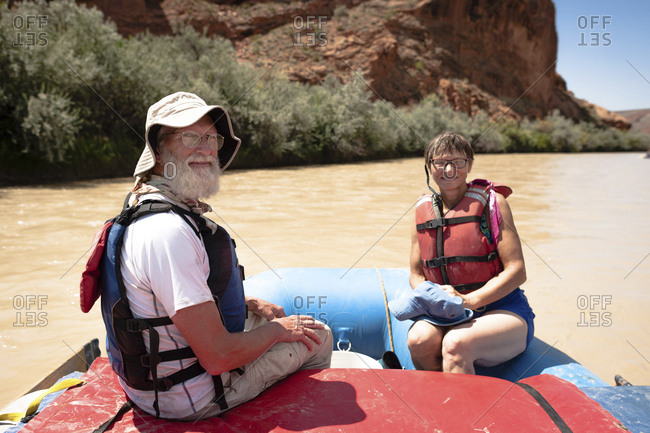 Portrait of senior man and woman sitting in inflatable raft on San Juan River