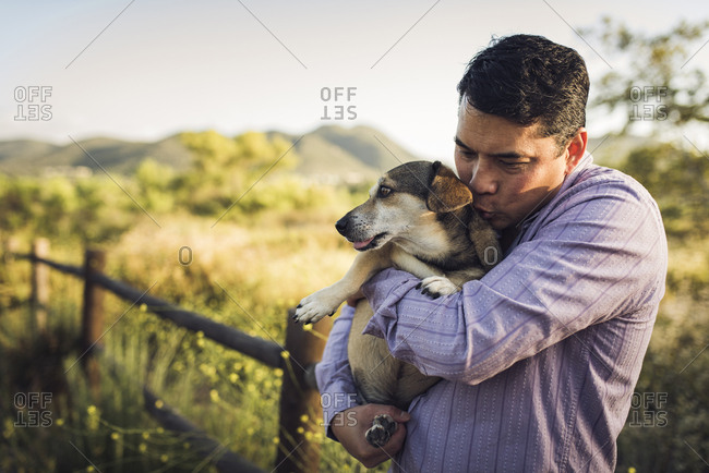 Man kissing dog while embracing it on field