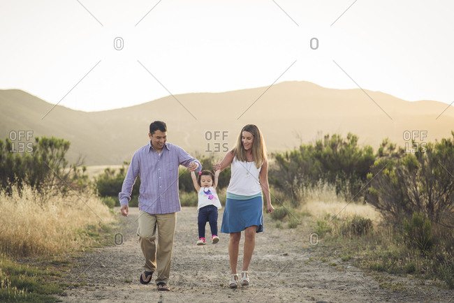 Happy parents lifting daughter while walking on field against clear sky