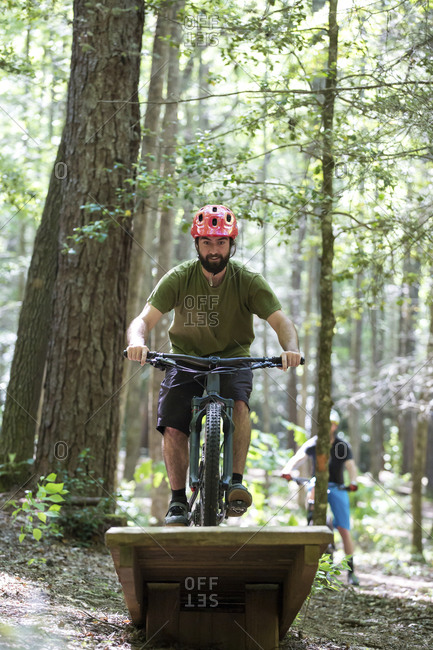 Hiker doing stunt while riding mountain bike with friend in background at forest