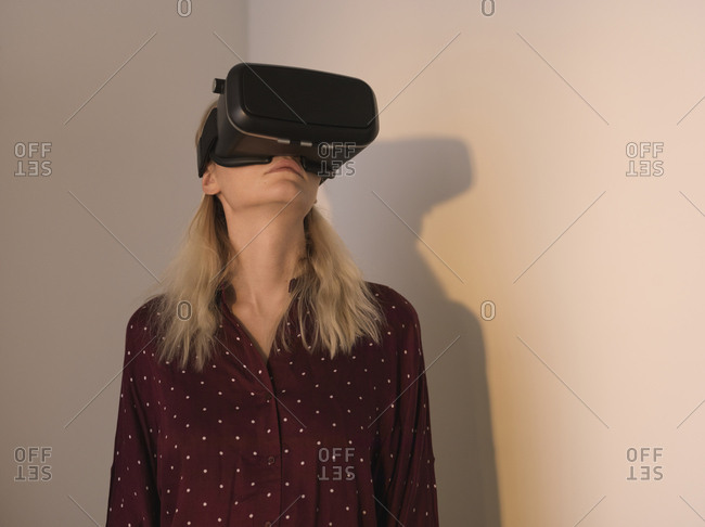 Woman using virtual reality simulator while standing against walls at home