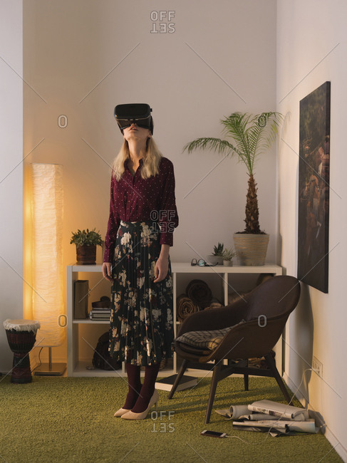 Full length of woman using virtual reality simulator while standing against wall at home