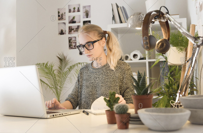 Businesswoman using laptop while sitting at desk by houseplants in creative office