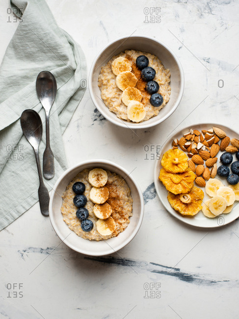 Two bowls of oatmeal with banana slices, fresh blueberries and cinnamon