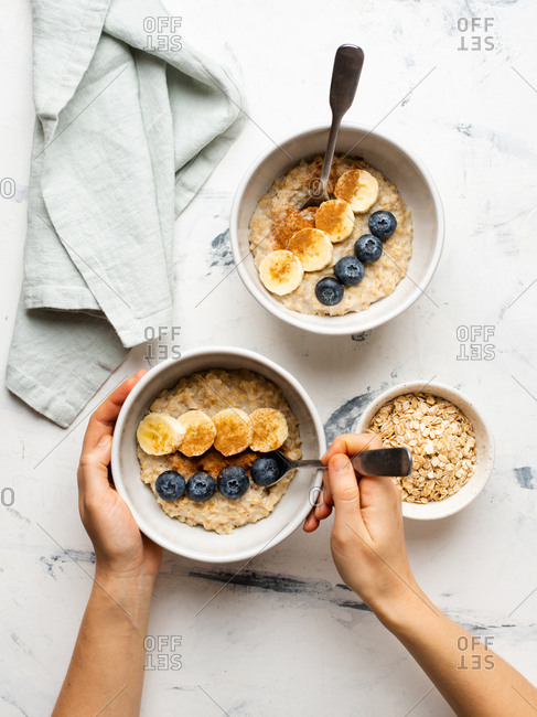 From above hands of person eating oatmeal served with banana slices and fresh blueberries