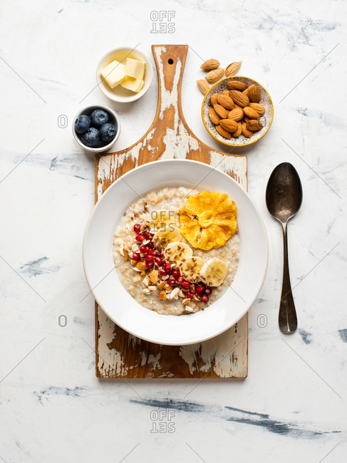 Oatmeal with sliced banana, linen seeds, dried pineapple and pomegranate