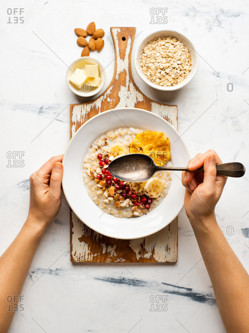 Hands of person eating oatmeal served with banana, linen seeds, dried pineapple and pomegranate