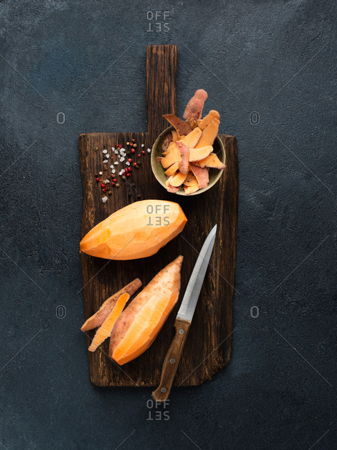 Peeled sweet potato on wooden cutting board with salt and pepper