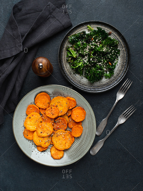 Sweet potato slices baked in oven served with warm kale salad with sesame