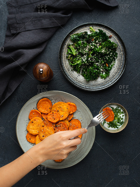 Sweet potato slices baked in oven served with warm kale salad