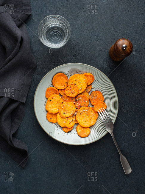 Plate with sweet potato slices baked in oven