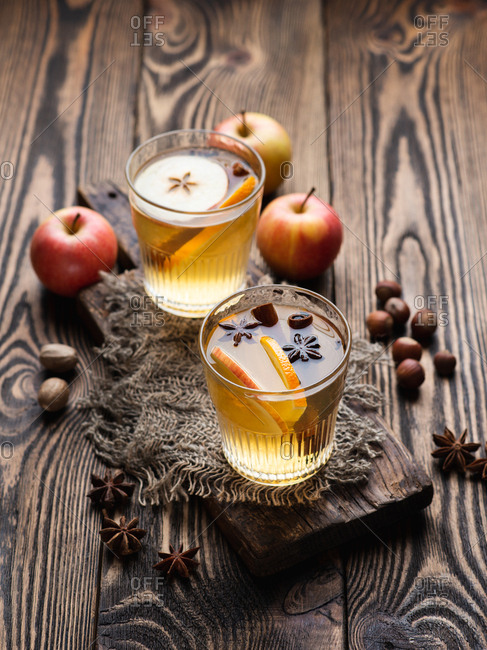 Hot apple cider cocktail with cinnamon, orange slices and star anise on wooden table