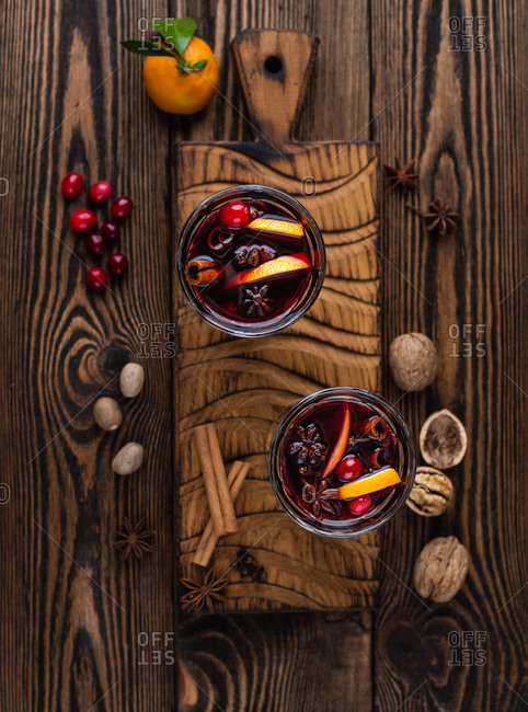 Two glass of mulled wine with cranberries, cinnamon sticks, orange and star anise on wooden board