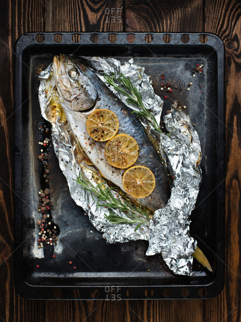 Overhead view of whole tuna fish baked with herbs, lemons, pepper and salt