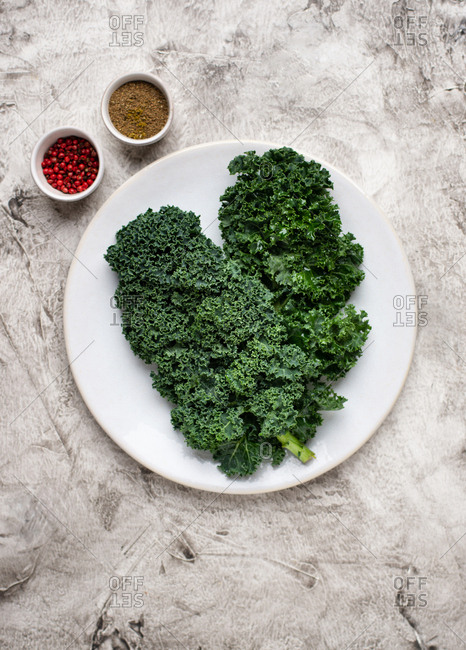Overhead view of fresh kale leaves on ceramic plate and spices