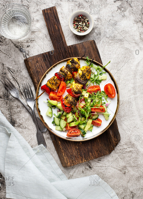 Skewers of chicken breast with grilled vegetables and vegetable salad on a plate