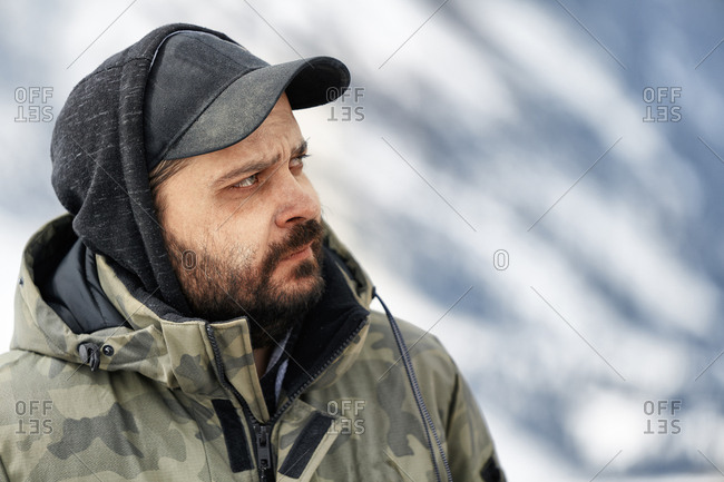 Middle aged man looking at scene in winter mountain area