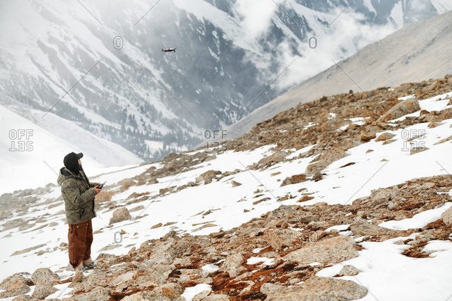 Mountaineer flying a drone to make videos and photos