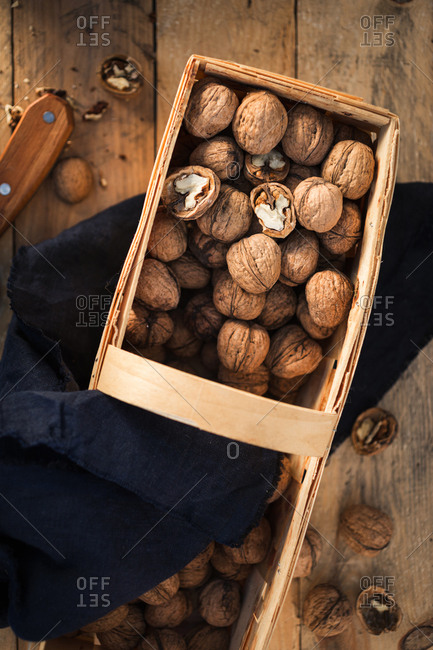 Whole walnuts and walnut pieces in wicker basket on wooden table