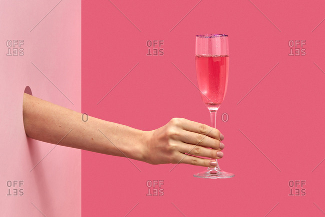 Holiday glass of rose wine in a female's hand through the hole in the wall on a duotone pink background with soft shadows, copy space. Holiday concept.