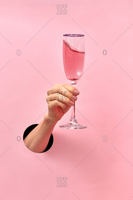 Woman hand from the hole holds glass with rose wine on a pastel pink background, copy space. Holiday concept.