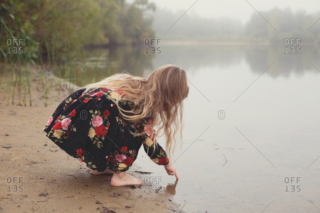 Little girl on a lonesome and foggy adventure dips finger in pond