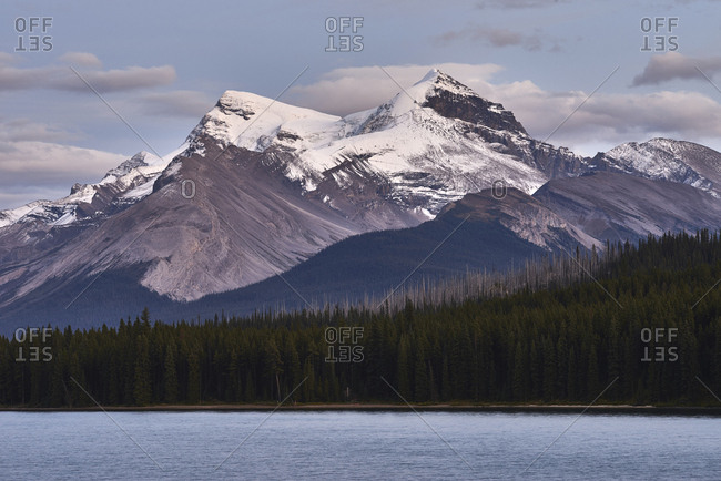 Scenic view of Maligne lake by snowcapped mountain against cloudy sky
