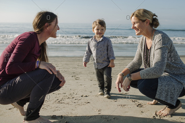 Lesbian couple looking face to face with son standing at beach against sea