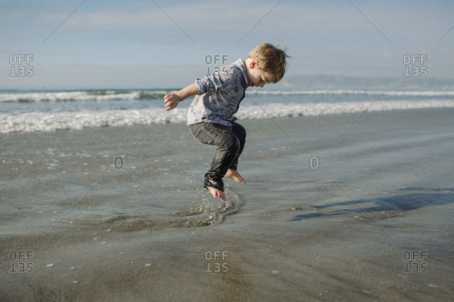 Playful boy jumping in water on shore at beach against sky