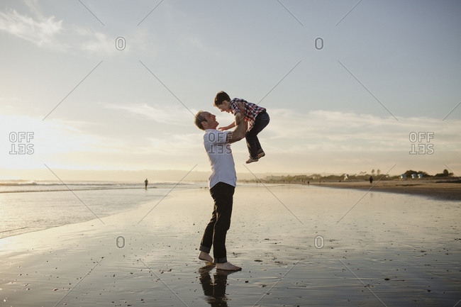 Playful father lifting son while playing at beach against sky during sunset