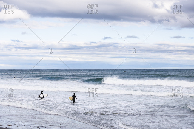 Women walking out for winter surf