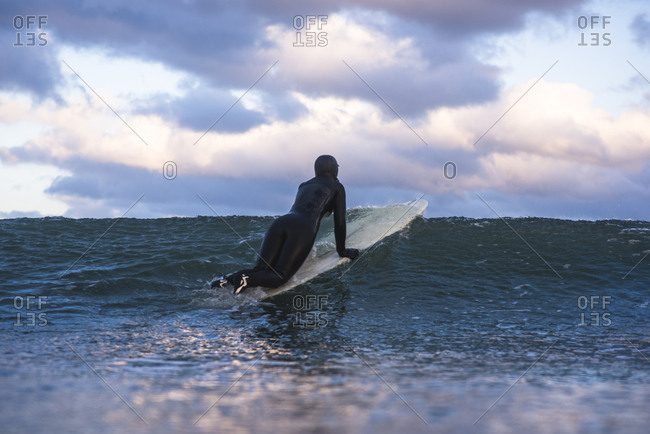 Woman surfing winter day at sunset