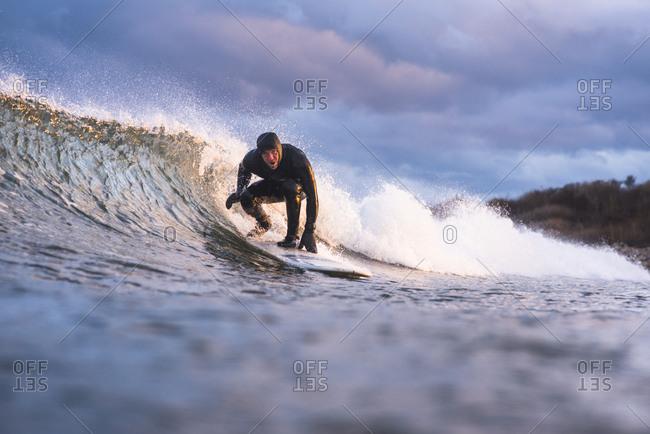 Rhode Island, Narragansett - January 30, 2019: Man surfing on a winter day at sunset