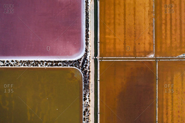 Aerial view of geometric and colorful salines near Cagliari, Italy.