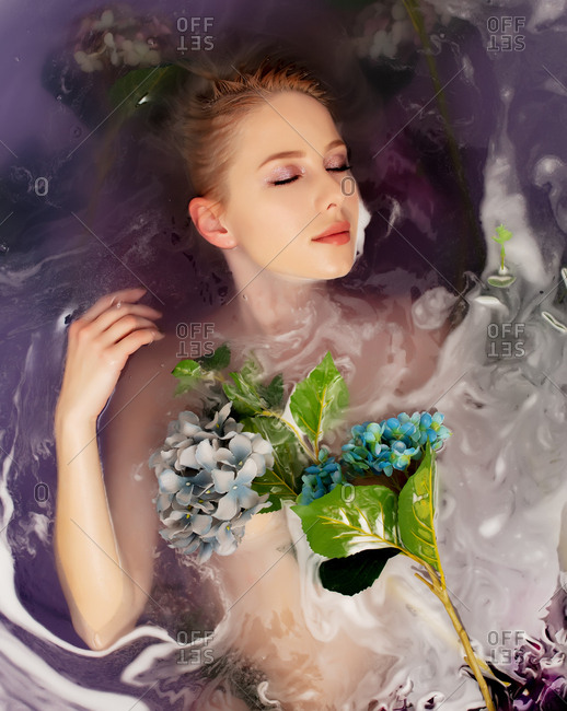 Beautiful woman covered in flowers lying in a bath tub filled with purple water