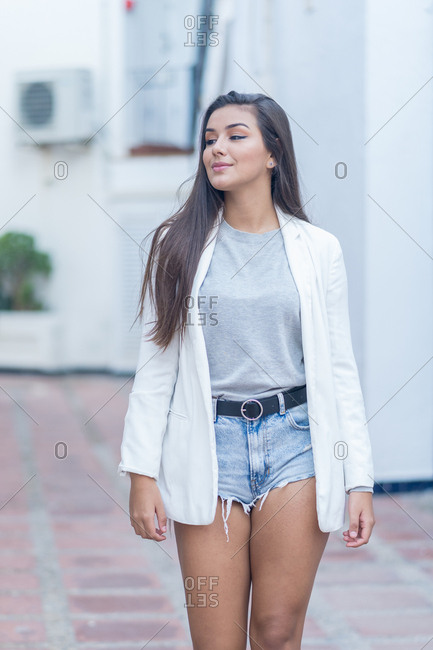 Young woman strolls distracted through the streets of a small town