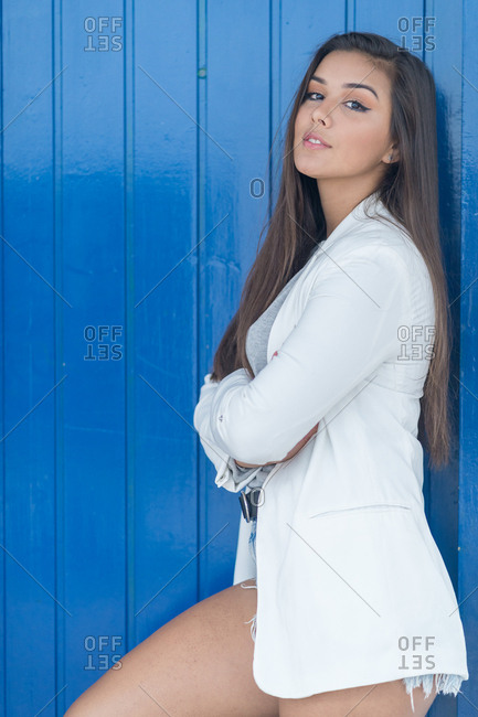Girl dressed in a white jacket poses supported by a blue door