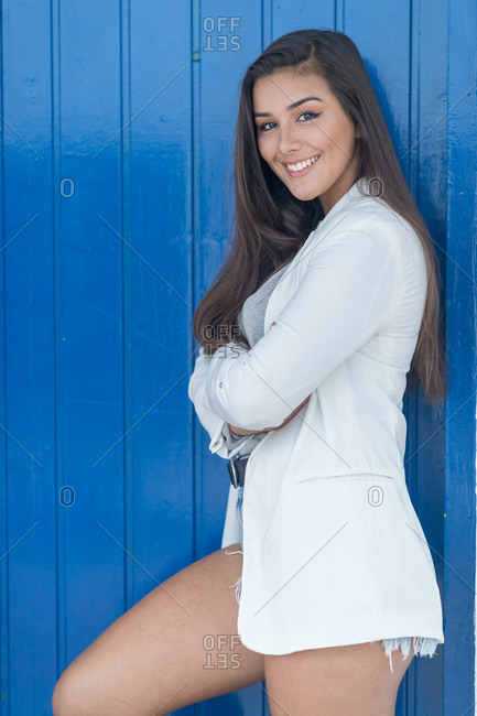 Girl dressed in a light-colored jacket poses supported by a blue door