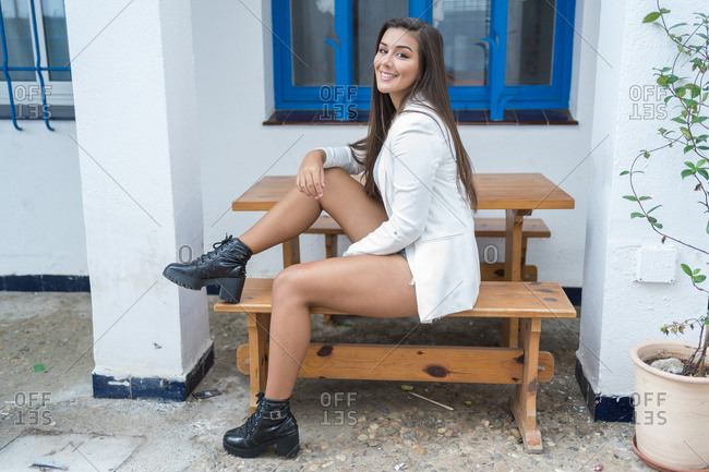 Happy young woman sitting on a wooden bench in a small village