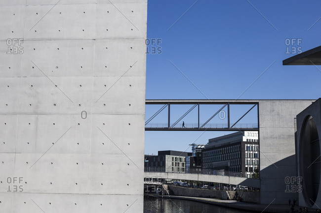 A person crosses an elevated walkway between government buildings in Berlin, Germany