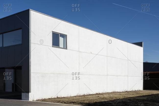 White exterior of modern building under blue sky