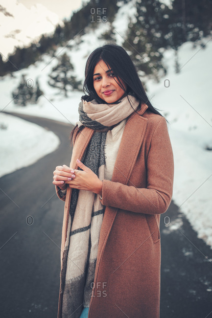 Young woman with dark hair standing on rural road in winter